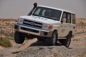 TAG White armored Toyota Land Cruiser (TLC) 76 Series cash-in-transit SUV with upgraded suspension in the desert