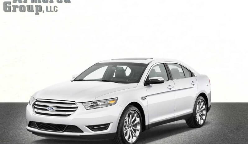 Picture of white armored Ford Taurus sedan with blast protection