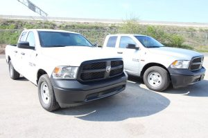 TAG Armored Dodge Ram 1500 Two White Trucks Parked Corner Side Front View Outdoors