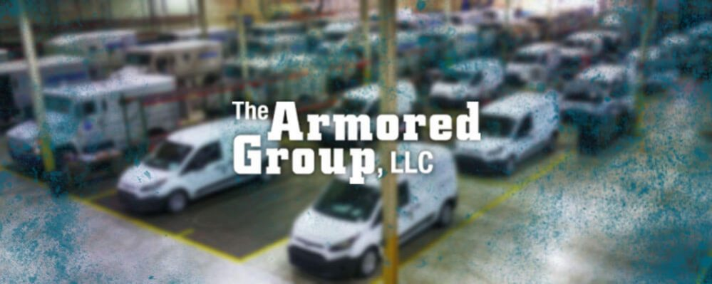 The Armored Group LLC Front Page Front Page Warehouse Multiple Vans Trucks Background